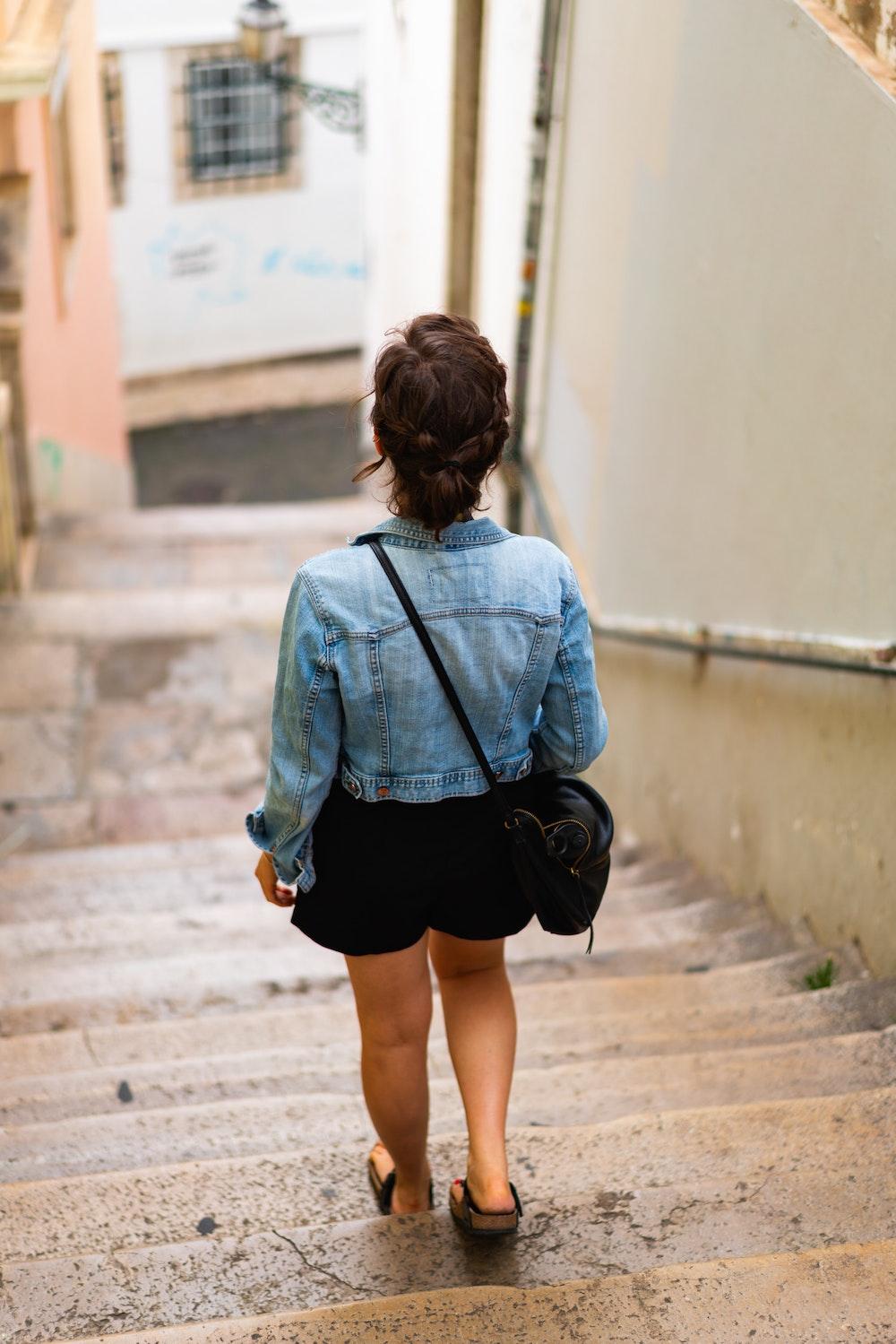 Girl walking on stairs in the Alfama neighborhood in Lisbon