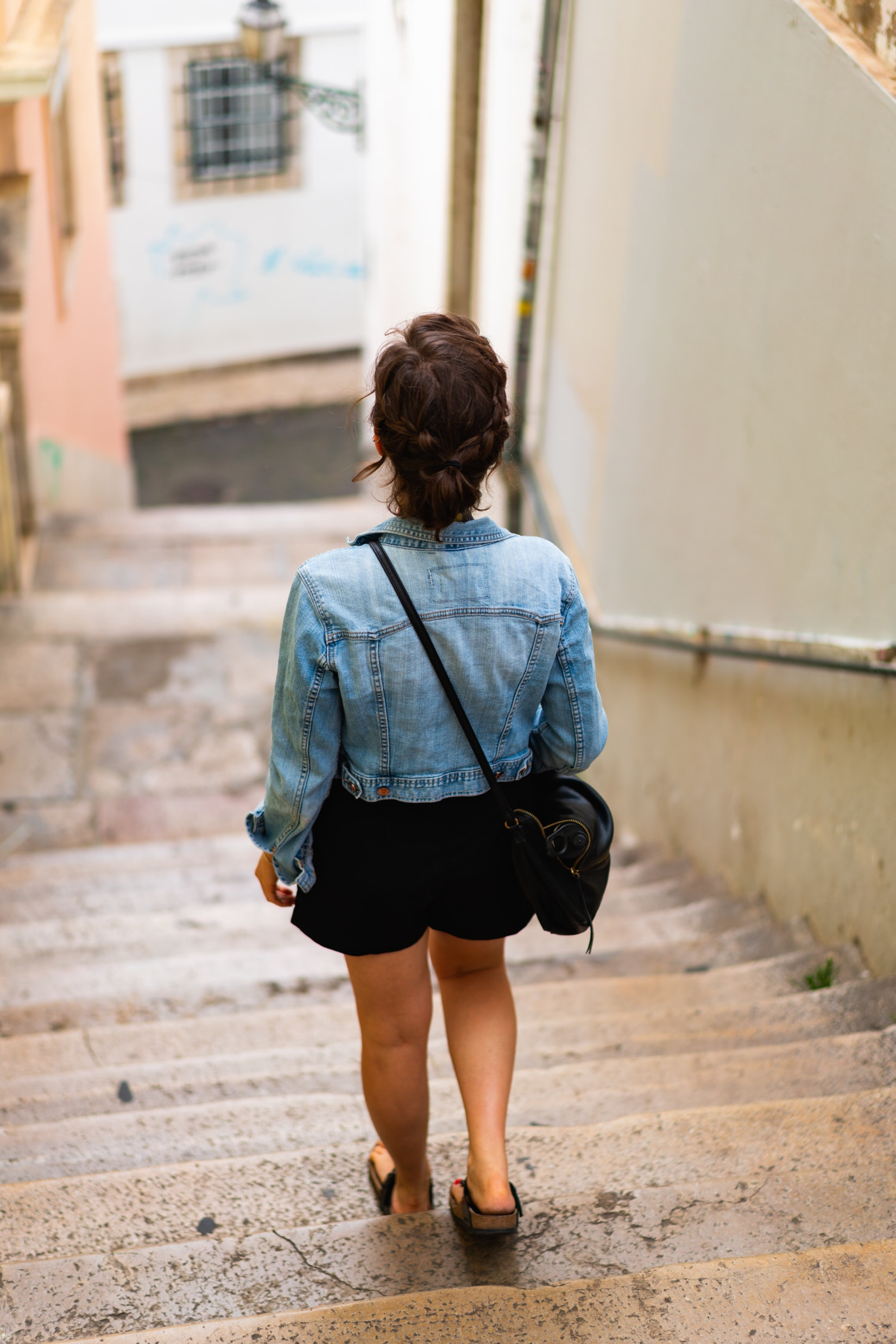 Girl walking on stairs in the Alfama neighborhood in Lisbon
