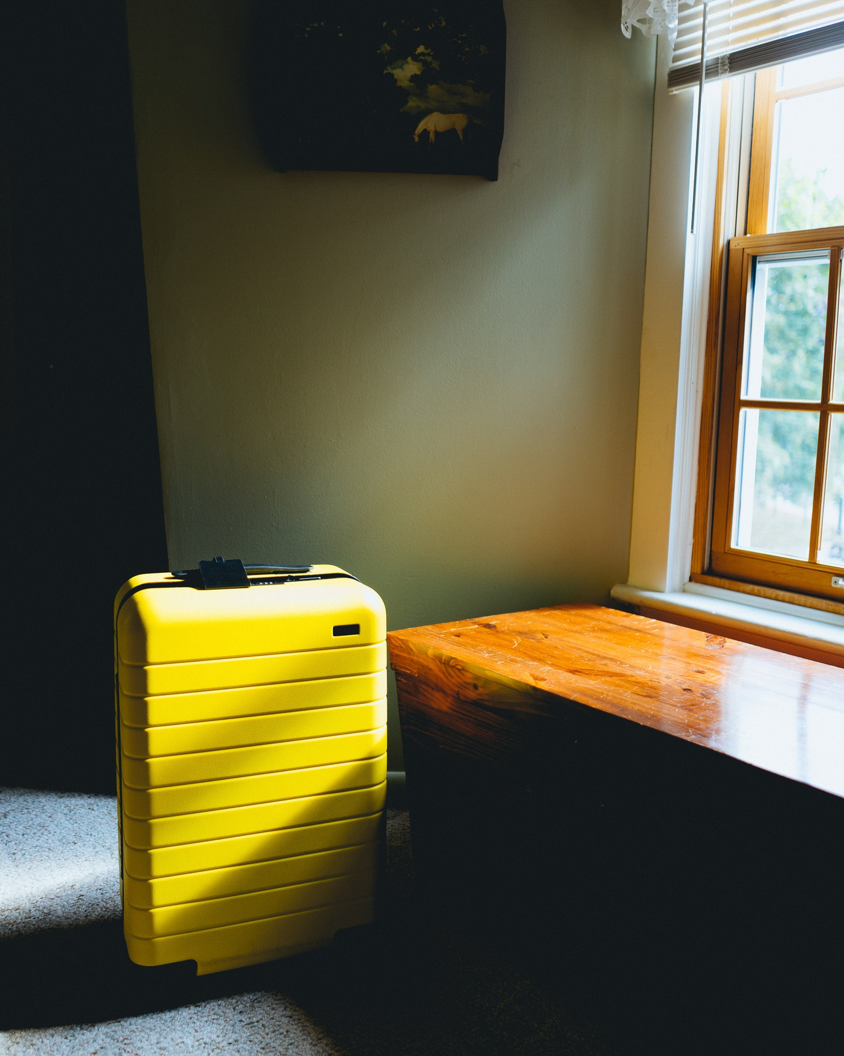 Yellow away suitcase in a room with sunlight
