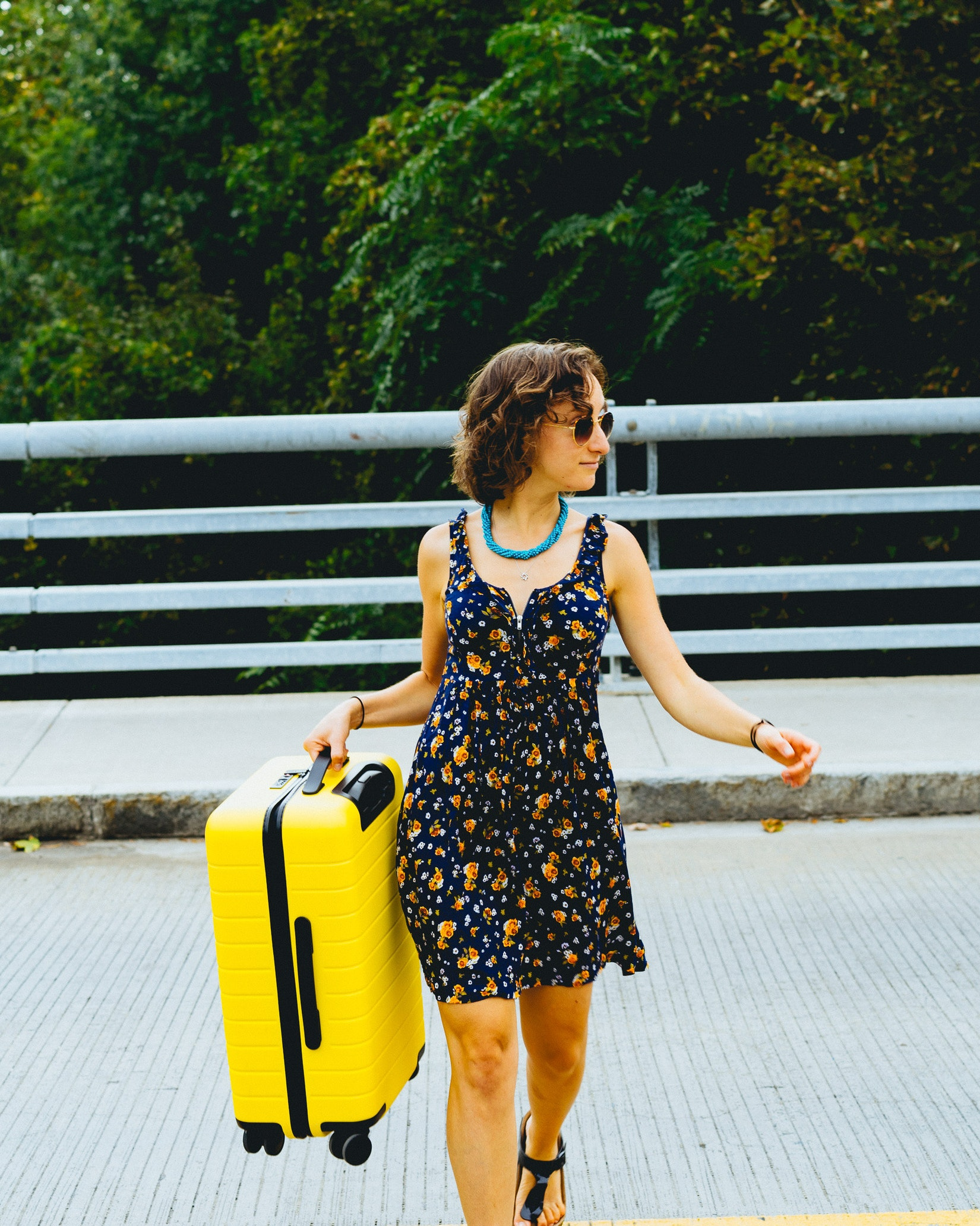 Girl not using the wheels of a suitcase even though that is a perfectly find thing to do