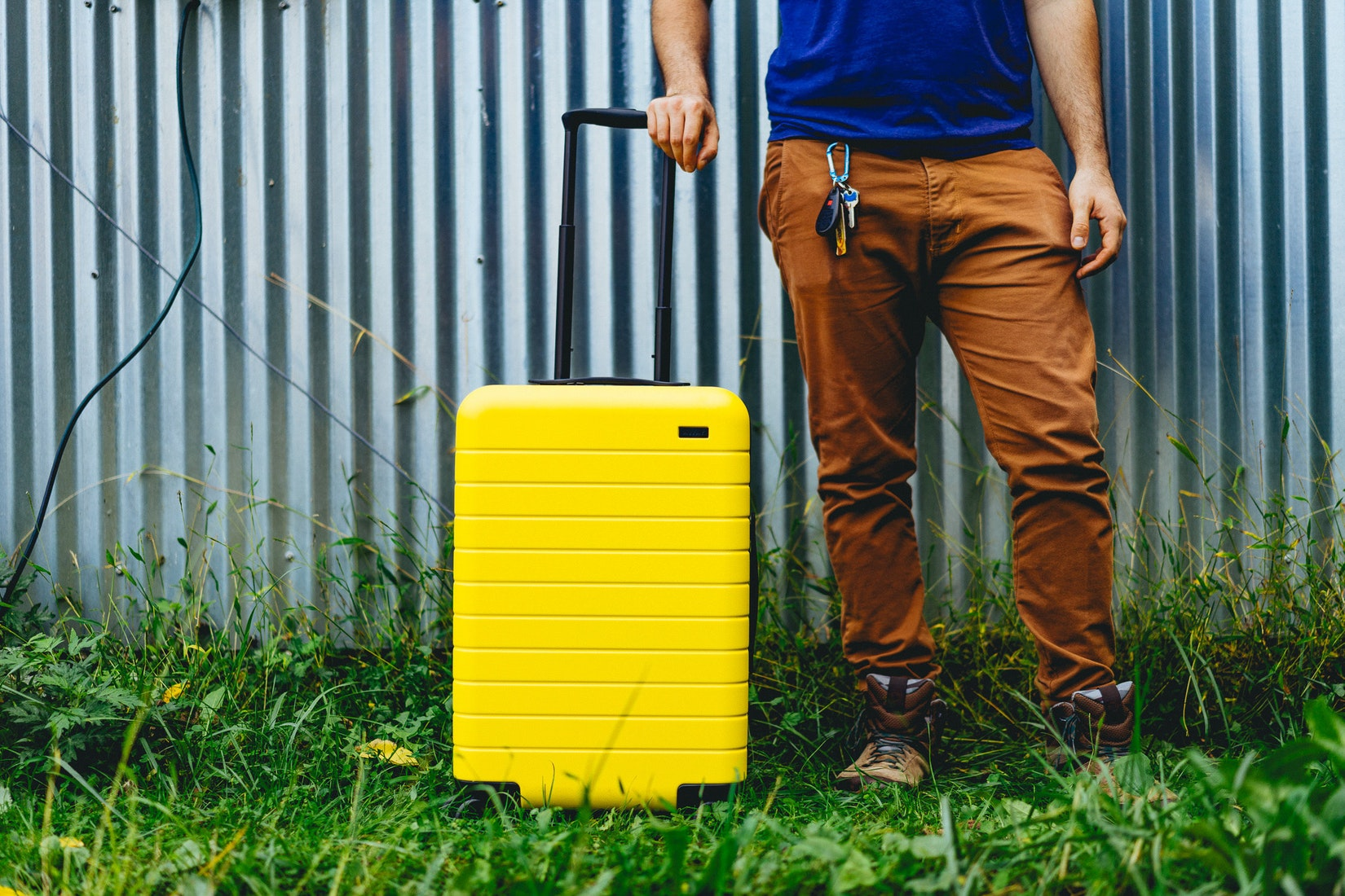 Man against a metal siding next to a yellow suitcase