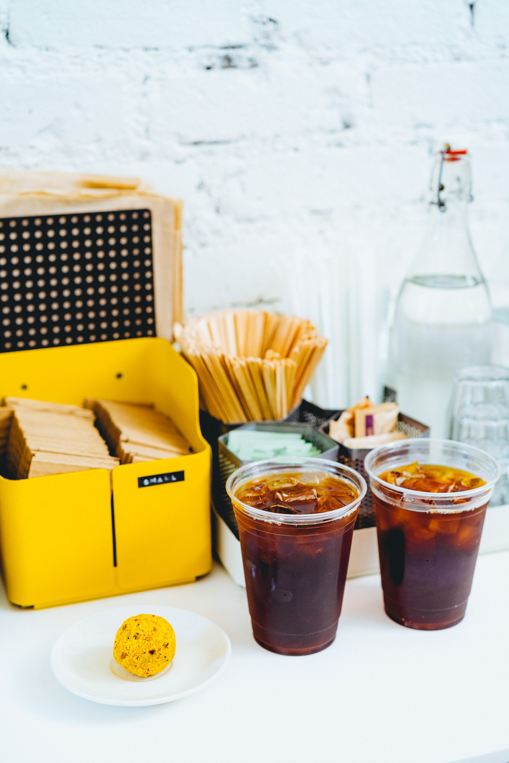 Two iced coffees sitting on a coffee station. The coffee station is where you prepare your coffee.