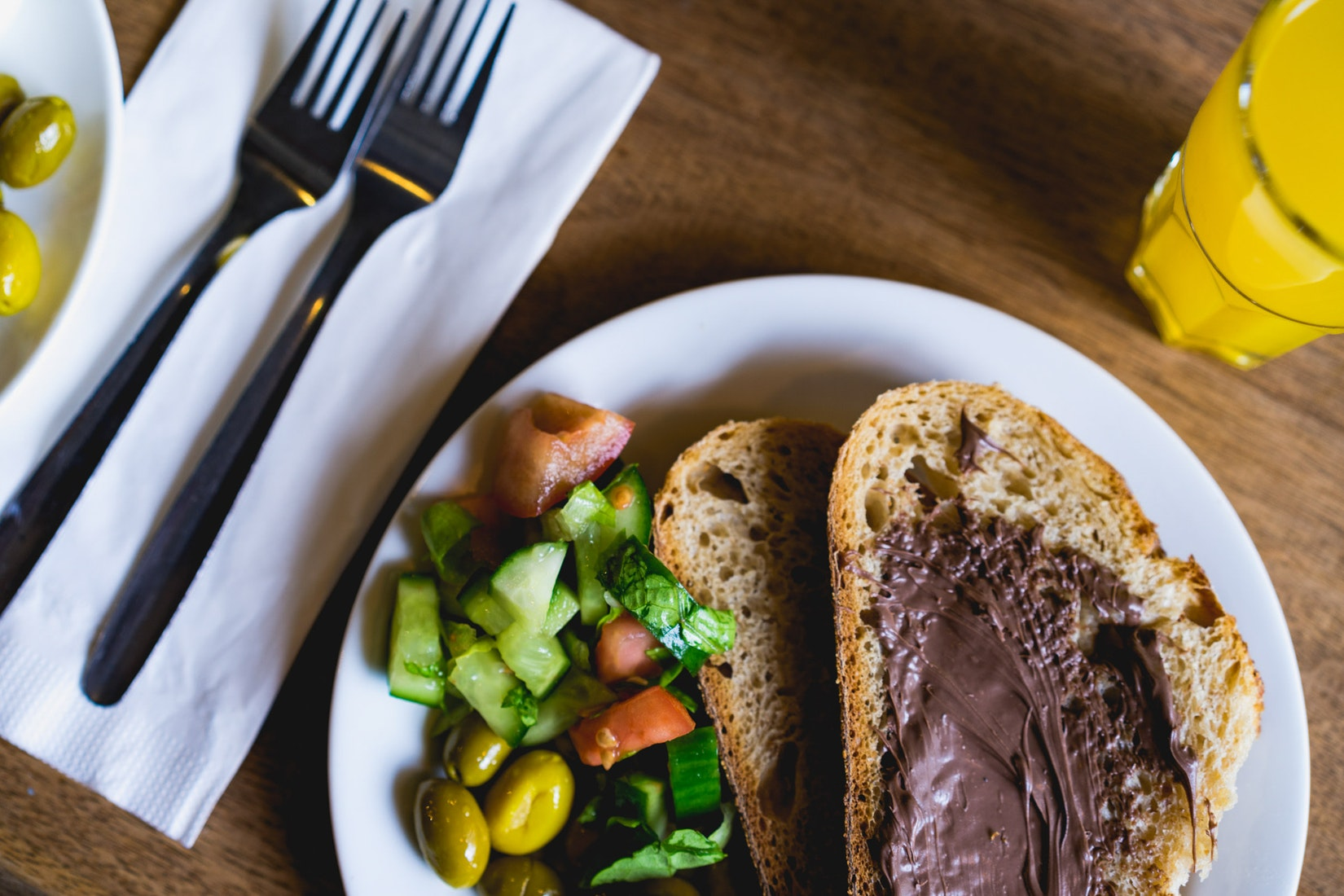Toast with Nutella, Israeli salad on a rustic bar.