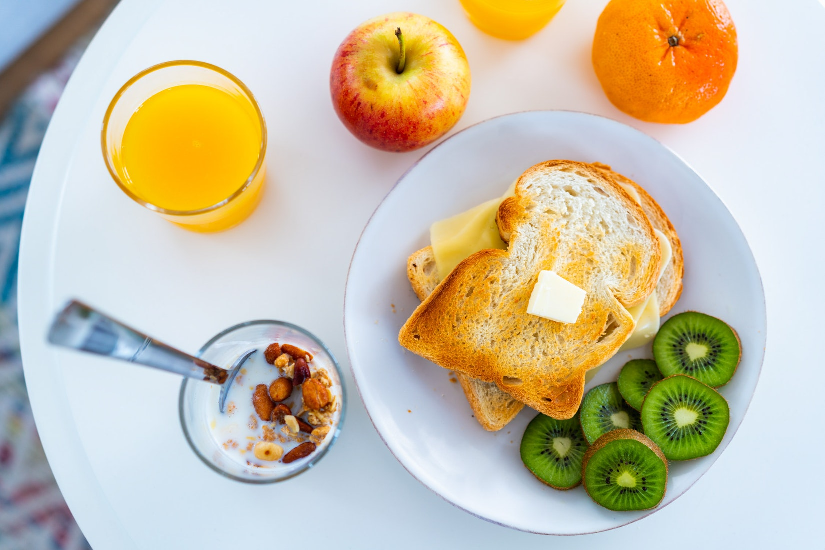 Healthy breakfast with cereal, toast, kiwi, orange juice, apples and oranges.