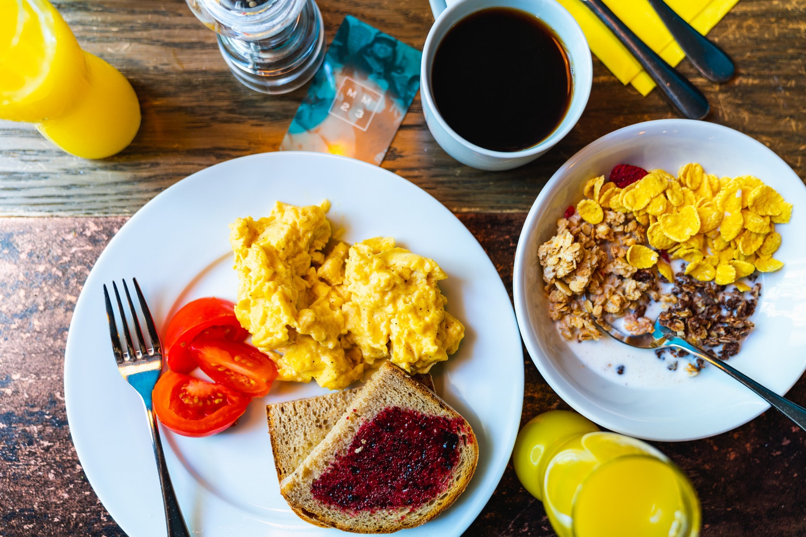 Big breakfast with toast, eggs, tomatoes, cereal, coffee and more!