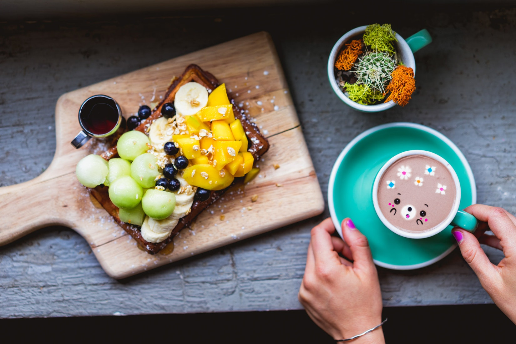 Loaded waffles with mellon, mango, banana and blue berries. On the side of the waffle is a bear latte.