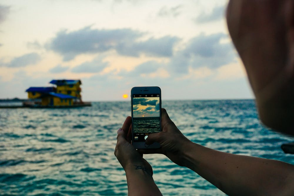 Girl taking photo of a house on the water at golden hour in Cartagena, Colombia