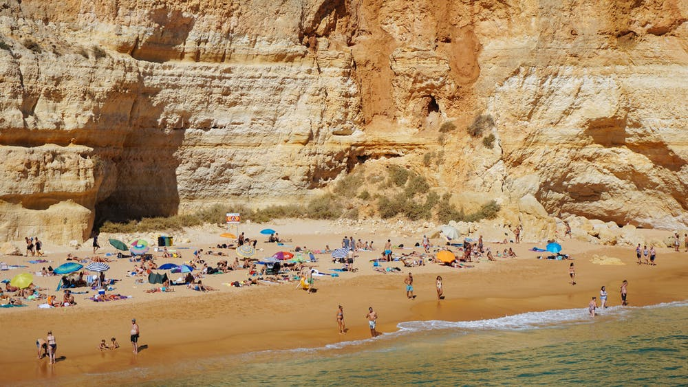 Crowded beach with tall rocks off the south coast of Portugal