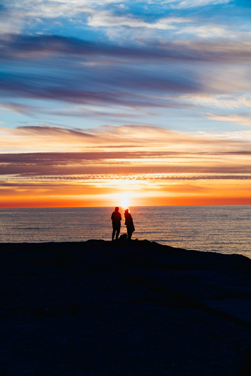 Two people at the edge of a rock during sunset at a beach