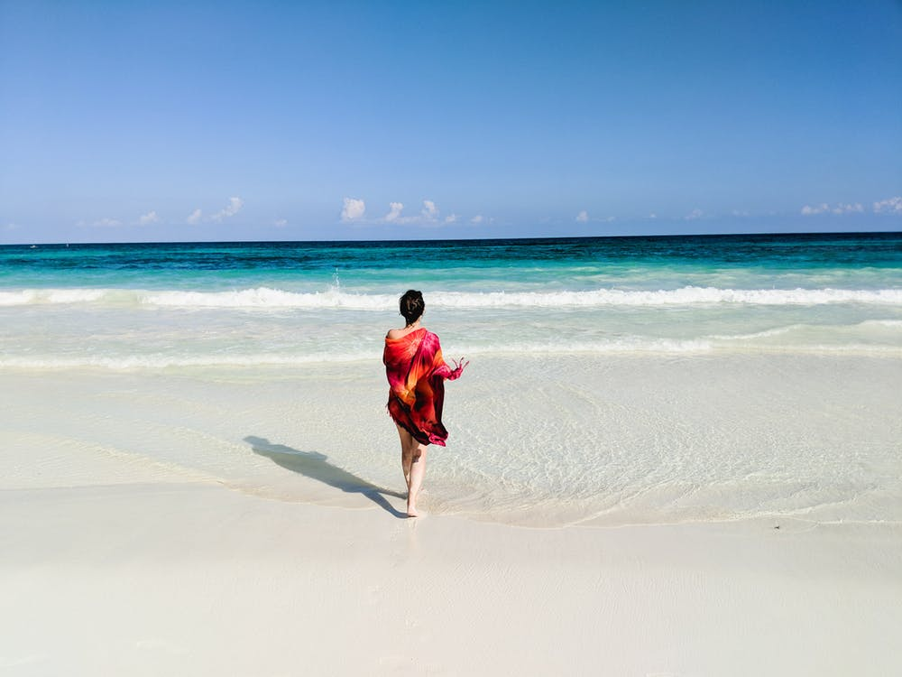 Girl with a red dress walking on a beach in Mexico