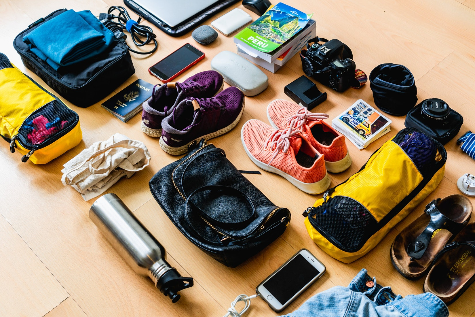 Items to pack while traveling. The items include shoes, cameras, electronics and books