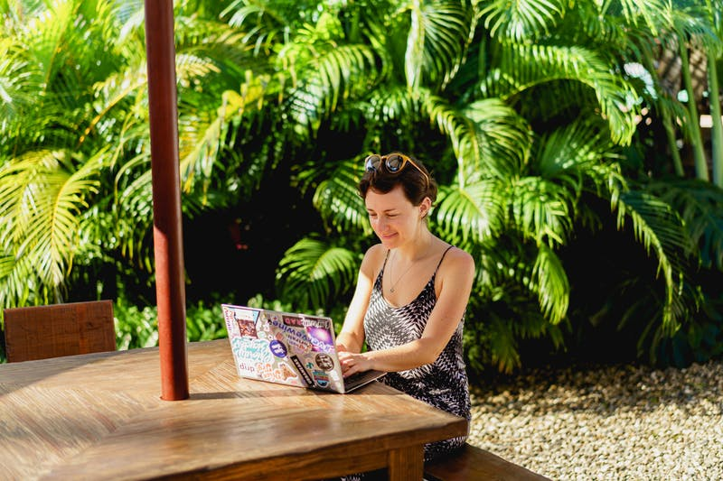 Yemyeşil tropik bitkilerle dolu ahşap masada dijital göçebe bir dizüstü bilgisayar olarak uzaktan çalışan kız