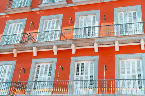 Beyaz panjurlu ve metal süslü balkonlu İspanyol tarzı turuncu bina