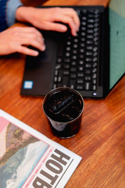 Siyah soğuk demlenmiş buzlu kahve, dizüstü bilgisayarda yazan bir kızın yanında.