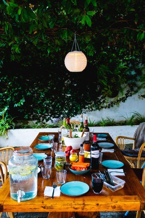 Mavi tabaklar, şarap şişeleri ve asılı bitkiler ve fener ışığı ile bir yemek için ahşap yemek masası seti