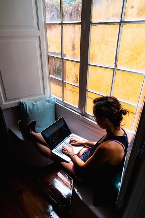 Tarihi bir evde beyaz bir cumbalı pencerede dizüstü bilgisayarda çalışan kız
