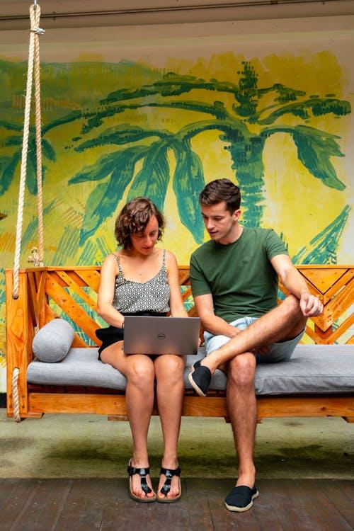 Selina'da sarı ve yeşil boyalı bir duvarın önünde bir dizüstü bilgisayarla asılı ahşap bir bankta oturan kadın ve erkek