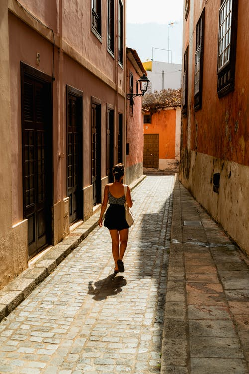 Kanarya Adaları'nda pembe ve turuncu boyalı duvarlar arasında tarihi bir dar sokakta yürüyen kız