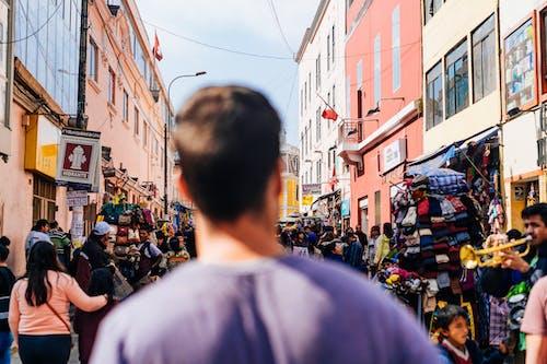 Lima Centro Historico'da kalabalık bir caddede yürüyen mor gömlekli adam