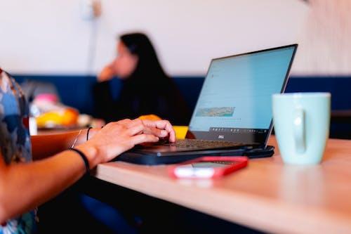 Kızın elleri masada beyaz kahve fincanı olan bir dizüstü bilgisayarda yazıyor.