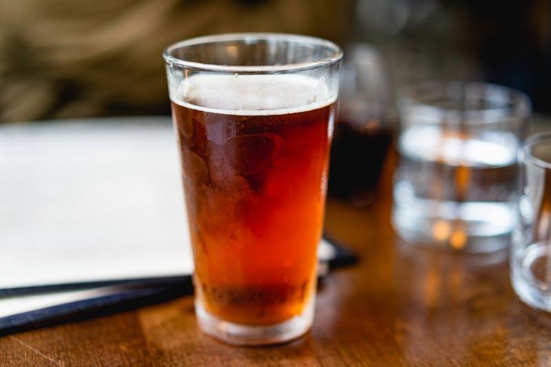 Ahşap bir masada beyaz menülerin yanında buzlu bira bardağı ve su bardakları.