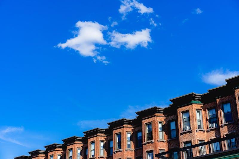 Back Bay Boston semtindeki tarihi sıra evlerin üzerinde mavi gökyüzü ve beyaz bulutlar