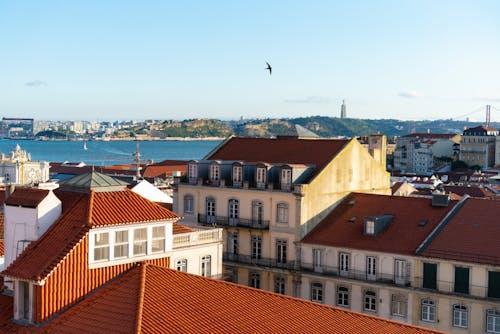 Lizbon'daki tarihi binaların ve mimarinin mavi gökyüzü, nehir ve kırmızı çatıları
