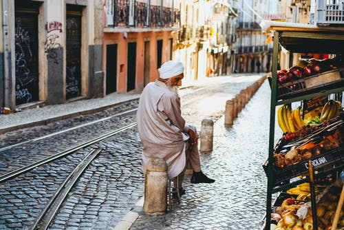 Lizbon Portekiz'de bir Arnavut kaldırımlı sokakta oturan beyaz türban giyen bej bir cüppeli adam