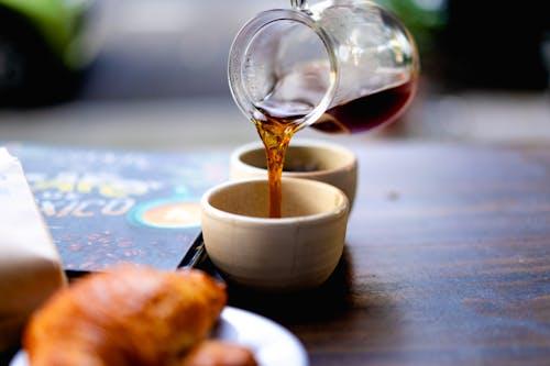 Ahşap bir masadaki cam sürahiden küçük beyaz bir bardağa sade kahve dökmek