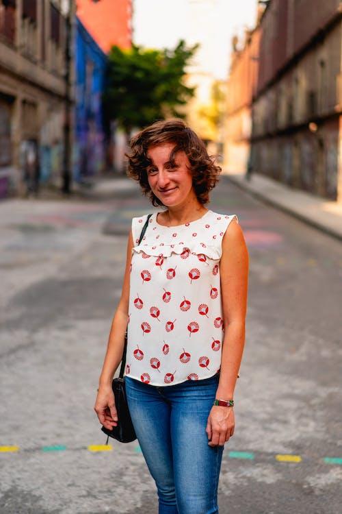 Mexico City'de sakin bir sokakta duran beyaz bluz ve kot giyen kız