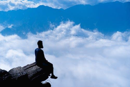 Sapa Vietnam'da mavi dağlar ve bulutlar arasında bir uçurumun üzerinde bir kayanın üzerinde oturan adam