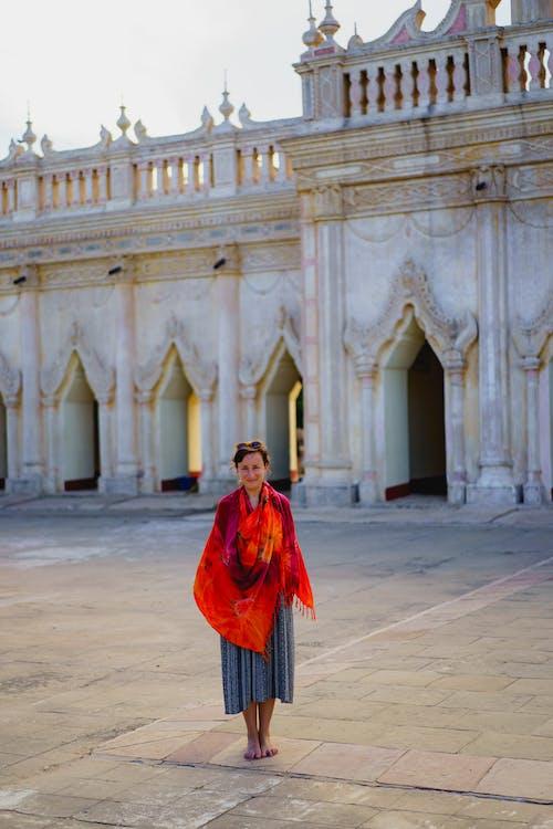 Bagan Myanmar'daki en büyük Budist tapınağında kırmızı ve turuncu Malaya peştemâli giyen kız