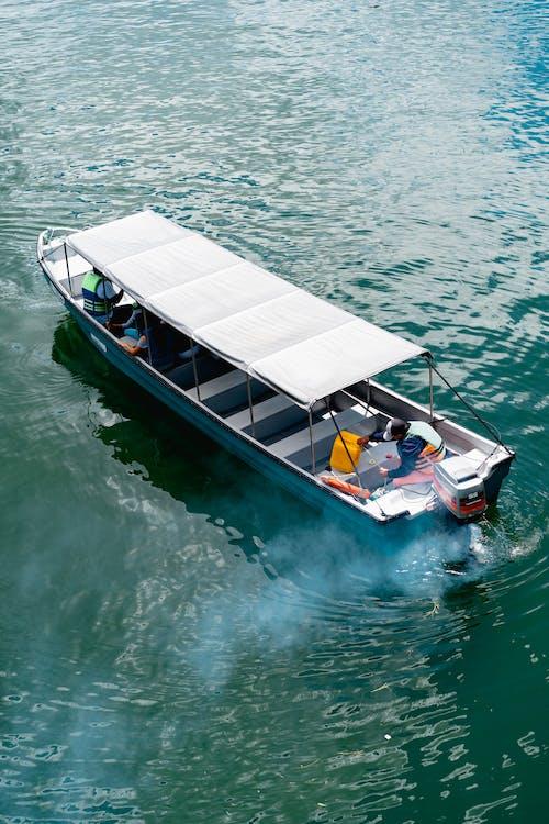 Bir nehirde arkadan çıkan çatı örtüsü ve duman ile motorlu tekne