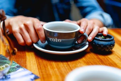 Bogota'da ahşap bir masada büyük bir mavi kahve fincanı üzerinde elleri olan kız