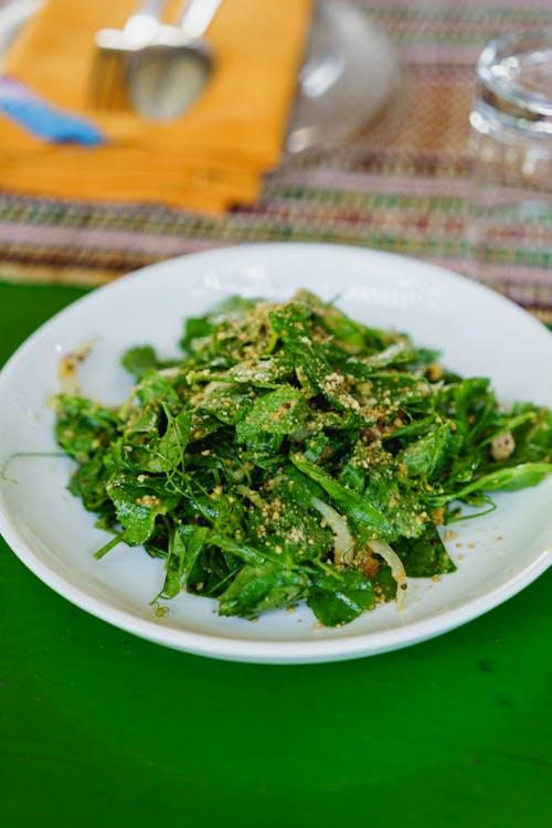 Aşçılık kursunda yeşil bir masada beyaz tabakta Birmanya çayı yaprağı salatası