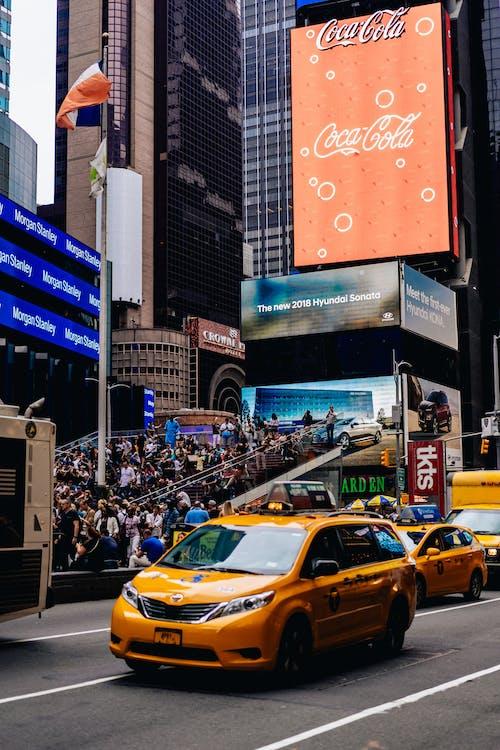 Büyük bir Coca Cola reklam panosu ve sarı NYC minibüs taksisi ile Times Meydanı sahnesi