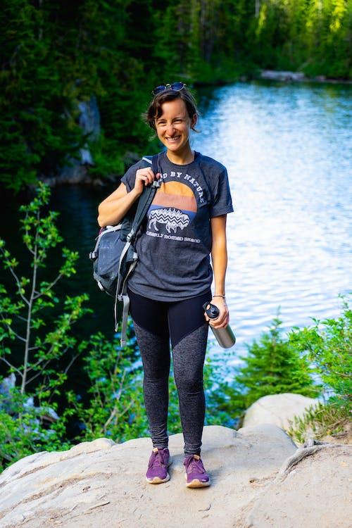 Mt Rainier Ulusal Parkı'nda bir nehirde tek omzuna asılmış sırt çantalı kız