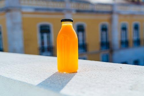 Güneşli bir günde Lizbon'da beton bir çıkıntının üzerinde cam şişe taze sıkılmış portakal suyu