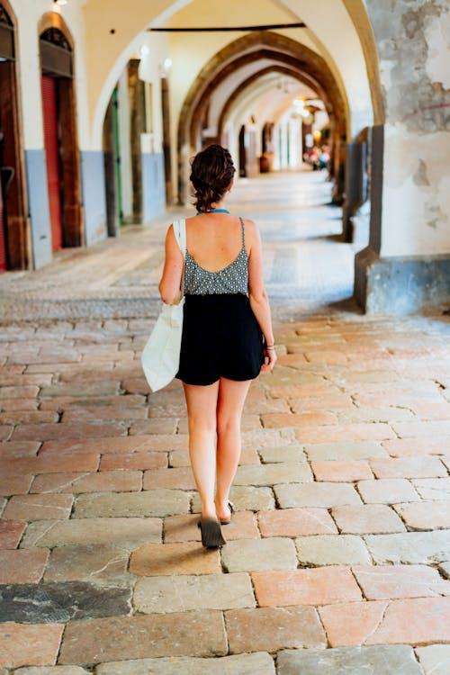 Tarihi Prag'da taş kemerli bir geçit üzerinde yürüyen kolsuz bluz ve siyah şort giyen kız
