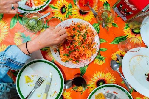 Kızın eli yumurta, kırmızı biber ve bitkilerle kaplı, turuncu bir masa örtüsünün üzerinde çiçeklerle kaplı bir patates kızartmasına uzanıyor.