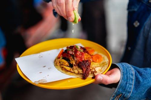 Mexico City'de sarı bir tabakta et döner tavuk taco üzerine limon dilimi sıkan kız