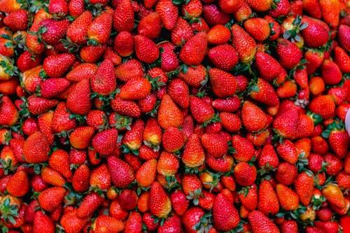 Bir pazarda yeşil yapraklı üstleri ile kırmızı çilek yığınları