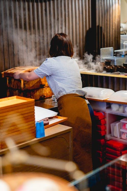 Taipei'deki bir pirinç ziyafeti dükkanında büyük bir bambu buharlı pişiriciyi ortaya çıkaran kadın