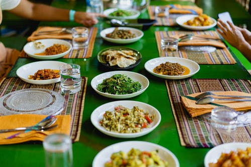 Yer ayarları ve Birmanya salatalarının beyaz tabakları ile yeşil ahşap masa