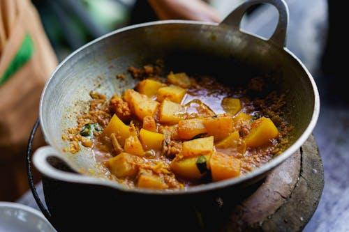 Ahşap bir masanın üzerinde gümüş bir tencerede kahverengi bir Burma köri içinde kaynayan patates parçaları