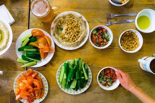 Beyaz tabaklar kesilmiş salatalık, nohutlu taze humus, dilimlenmiş domates ve İsrail salataları ile ahşap masa