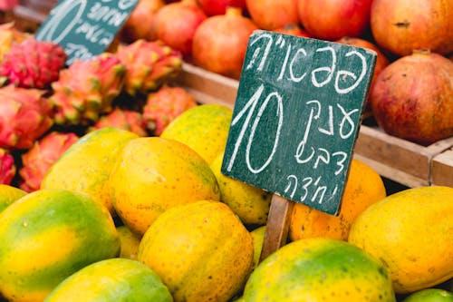 İsrail pazarında mango ve ejderha meyveleri arasına yerleştirilmiş İbranice yazı tahtası işareti