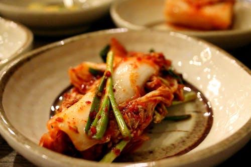 Beyaz bir tabakta üzerinde otlar bulunan tek bir parça kimchi
