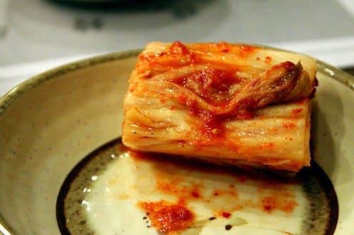 Beyaz tabakta kırmızı soslu beyaz kimchi parçası.