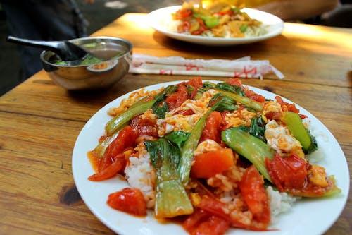 Kızarmış Çin domatesini ve yumurtayı beyaz tabakta pirinç üzerine servis edilen Çin lahanası ile karıştırın.